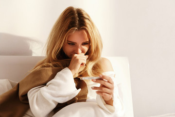 Ill blonde woman lies with a scarf in the bed and checks her temperature