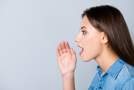 Hey, listen here! Close up side-view portrait of attractive woman telling news, shouting and holding hand near her open mouth, standing over grey background with copy space