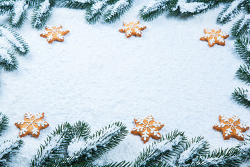 Christmas background with gingerbread cookies with snow and tree branches. Free space