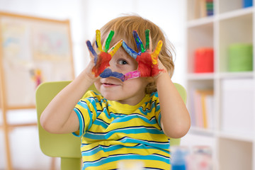 cute cheerful kid boy showing hands painted in bright colors