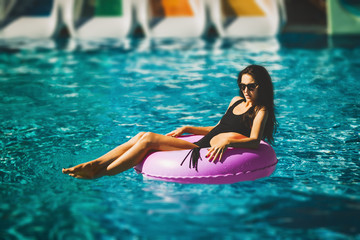 pretty beauty model in black bikini on the inflatable ring in the swimming pool. Summer Vacation. Enjoying suntan. Weekend on resort