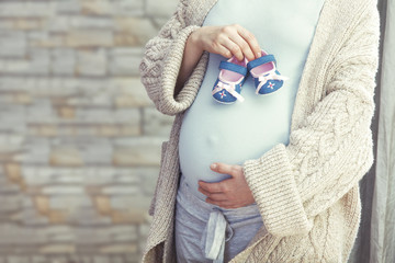 Pregnant woman with baby shoes near belly