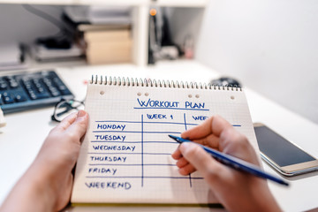 Close-up Of A Person's Hand Writing Workout Plan In Checkered Pattern Notebook