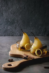 Traditional dessert poached pears in white wine served in glass bowls with syrup and lemon zest on wooden serving board over gray texture table.