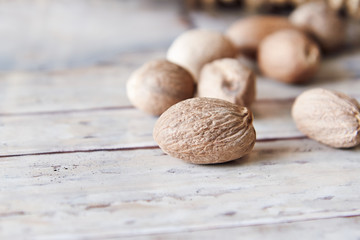 Fototapeta Nutmeg seeds on white rustic background. Copy space obraz