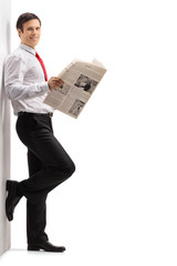 Formally dressed man with a newspaper leaning against a wall