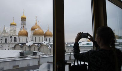 A woman takes a picture of the Ivan the Great Bell Tower on the territory of the Kremlin in central Moscow
