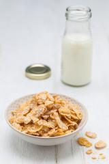 Cornflakes in einer Schale und Milchflasche