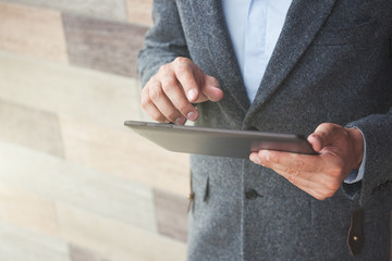 handsome businessman holding digital tablet touching with finger