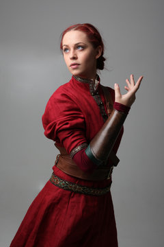 portrait of red haired girl wearing red medieval out fit, studio background.