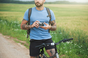 handsome man taking photo with camera traveling by bicycle