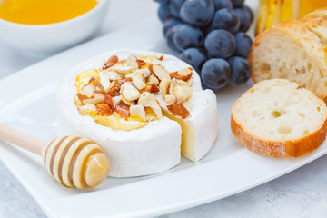 Brie cheese (camembert) with honey, nuts, baguette and fruit