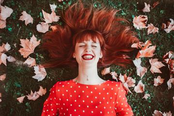 Cheerful woman posing on meadow in leaves