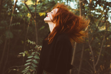 Redhead woman waving with hair on nature