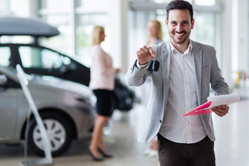 Handsome salesman at car dealership selling vehichles