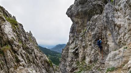 Woman climbing a ladder on the Via Ferrata at the Grigna Settentrionale (2408 m, Grignetta), Lake Como, Italy