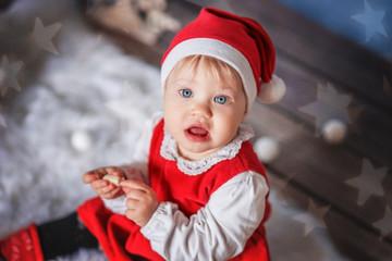 Little girl in Santa hat on Christmas background.