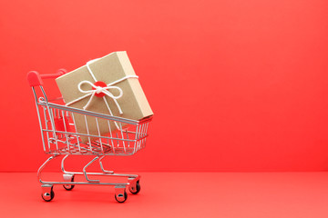 brown gift box in shopping cart on red paper background