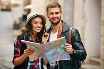 Happy Tourists. Beautiful Couple Sightseeing, Using Map.