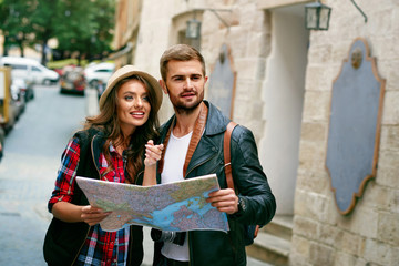 Couple Of Travelers Using Map For Sightseeing In Town.