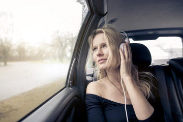 Portrait of young woman sitting in car listening music with headphones