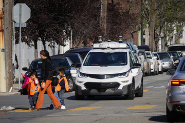 Children pass by a self-driving Chevy Bolt EV car during a media event by Cruise, GM's autonomous car unit,  in San Francisco