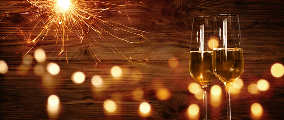 Champagne and sparkler in front of a wooden wall