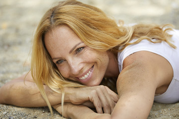 Portrait of happy strawberry blonde woman lying on the beach