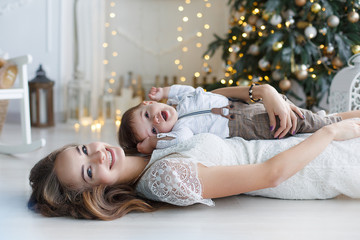 Happy mother and little son near christmas tree on Christmas. A woman and a little boy are resting in the white bedroom near the Christmas tree.  Mother plays with her son waiting for the New Year