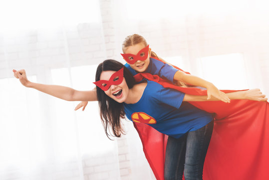 Mother with doughter in red and blue suits of superheroes. They in masks and in raincoats.