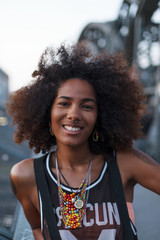 Young afro-american woman smiling on a steel bridge in urban scenery, Hackerbruecke bridge, Munich, Bavaria, Germany