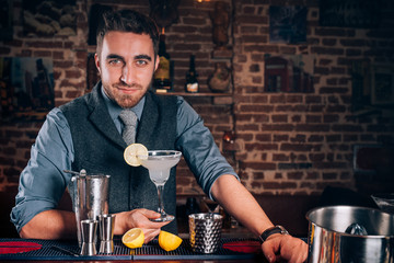 Portrait of beautiful barman making cocktails, signature margarita drink at local bar