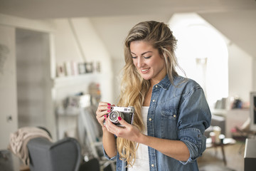 Indoor smiling lifestyle portrait of pretty young woman with camera