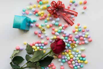 Top view blue gift box, ribbon, Colorful balls and red rose on white background.