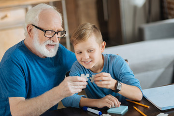 Pleasurable entertainment. Happy cheerful elderly man sitting with his grandson and holding a puzzle piece while collecting them together with him Wall mural