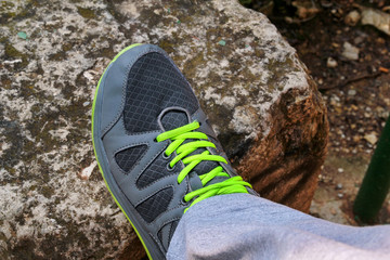 Male shoelaces on a running sneaker, close up. Part of sportsman sneakers. Lower part of a leg on a rock. Men's sportswear, Athlete's foot, sweatpants, a sneaker. Healthy lifestyle concept.