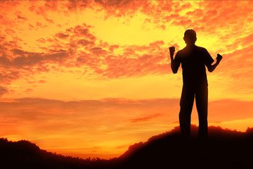 Happy celebrating winning success at sunset or sunrise standing elated with arms rose up above her head in celebration of having reached mountain summit