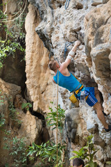 Young man rock climbing on white mountain