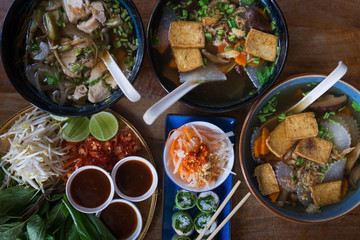 Traditional Vietnamese food. Soups, rolls and fresh herbs. Plates on a wooden surface. View from top to bottom.