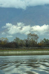 Harmony of nature - a sky with clouds, trees in autumn decoration over the lake waters