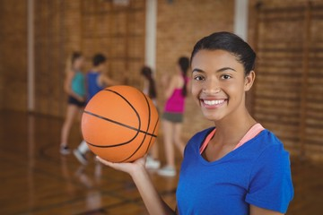 Smiling high school girl holding a basketball while team playing