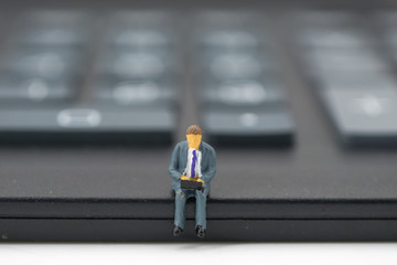 Miniature people: businessman sitting on calculator