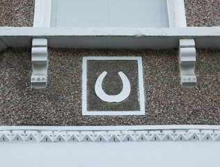 Image of a horseshoe on a wall of a house. Horseshoe is a symbol of good luck and happiness.