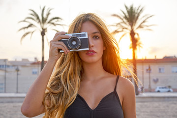 Teen girl with retro photo camera at sunset