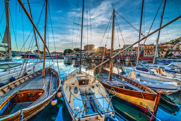 Wooden boats in La Maddalena harbor at sunset