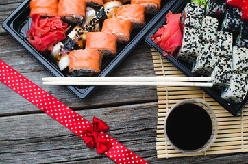 Sushi in a black container on a wooden table colorful and beautiful