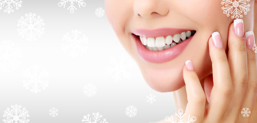 Closeup shot of woman's toothy smile against a grey background with snowflakes