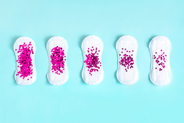 Menstrual pad with bright purple glitter on blue colored background. Woman periods cycle, menstruation frequency. Minimalist still life photography concept