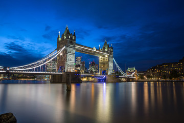 Famous Tower Bridge in the evening with blue sky and reflex on water, London, England