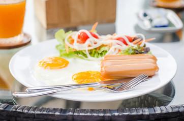 Breakfast, sausages, salad (mixed vegetable), eggs, glass of orange juice, bread and Thai dessert (Kanom Thai) at Chanthaburi, Thailand